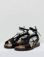 ASOS - FIZZLE - Sandali a pianta larga in gomma morbida con laccetti alla gamba - Nero